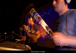 picture of The sancho Plan Drumming with bright coloured band blurred on fast moving drumsticks