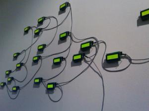 An image showing small screens on the wall with wires hanging from them