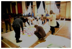A photo showing the group working on a huge piece of paper on the floor in a hall.